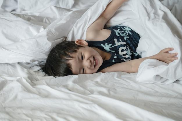 朝の楽しい動きとベッドの上のアジアの子供のクローズアップ Premium写真