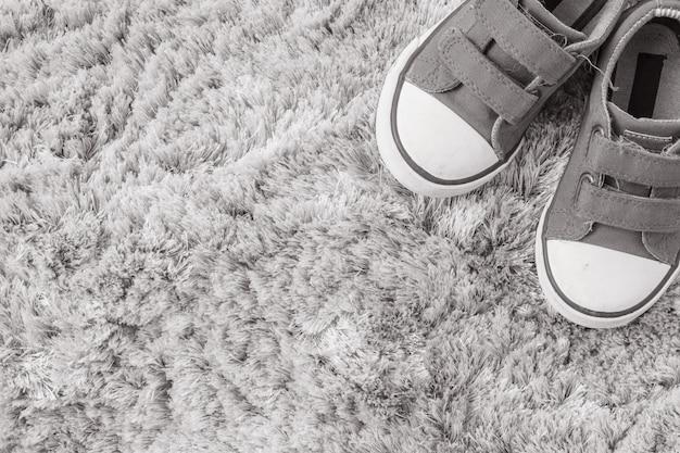 灰色のカーペットのテクスチャ背景の子供のクローズアップ生地スニーカー Premium写真