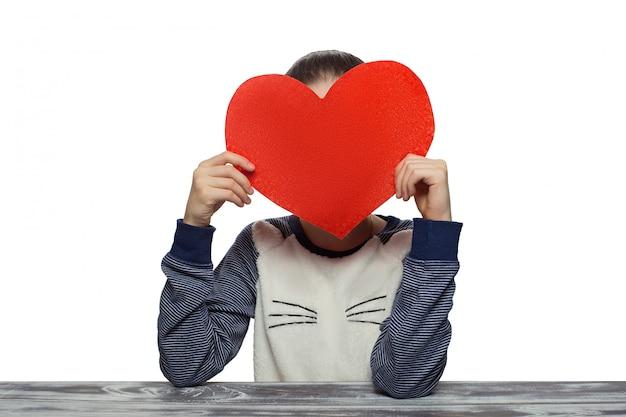 バレンタインデーのコンセプト-赤いハートを持つ少女。スタジオホワイトバックグラウンド女性モデルに分離 Premium写真