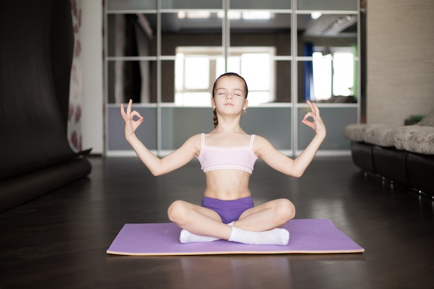 Маленькая кавказская девушка сидя на циновке в представлении и размышлять йоги. Premium Фотографии