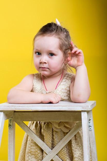 黄色の背景に椅子と美しいドレスの少女 Premium写真