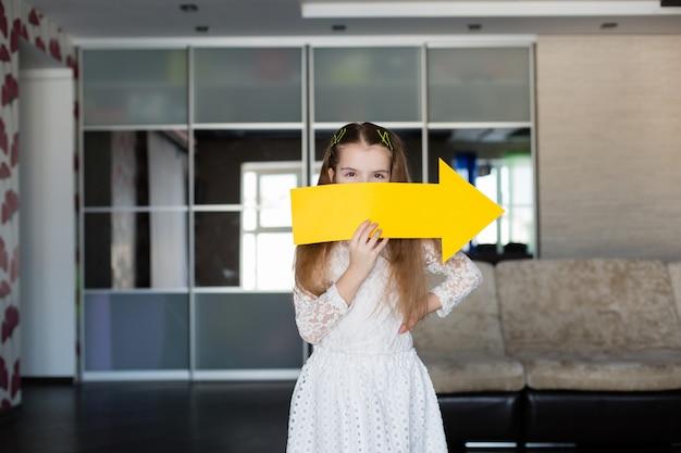 右向きの矢印の形をした空白の黄色い看板を持っているかわいい女の子 Premium写真