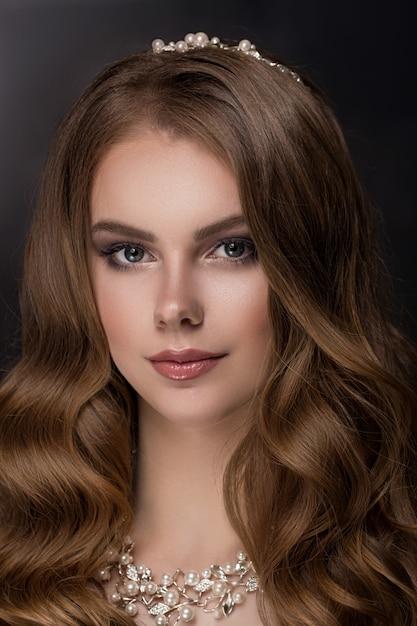 長くて光沢のある巻き毛を持つブルネットの少女。 Premium写真