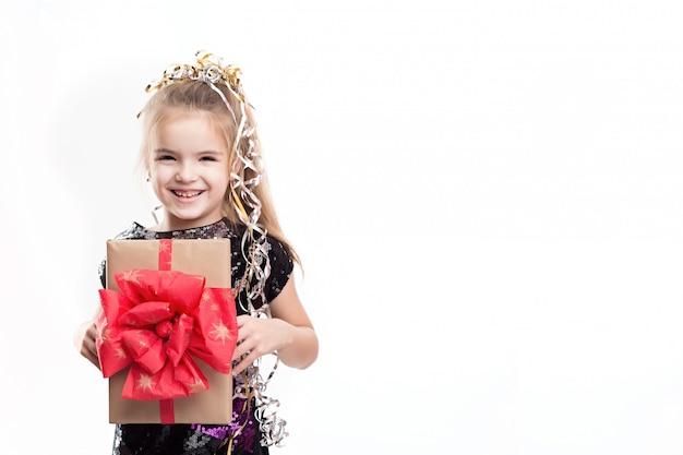 白い壁にギフトボックスを持つ美しい少女の写真 Premium写真
