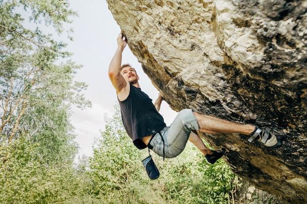 崖の上にぶら下がっている男性ロック・クライマー Premium写真