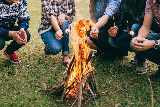 マシュマロを火で焼いている友人 Premium写真