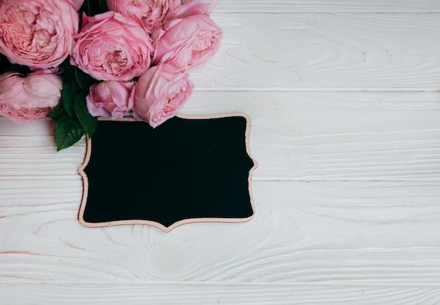 ピンクのバラと白いテーブルの上の額縁 Premium写真