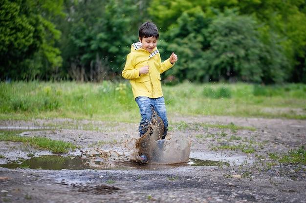 Мокрый ребенок прыгает в луже. веселье на улице. Premium Фотографии
