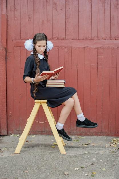 黄色の階段の上に座って本を持つ女子高生 Premium写真