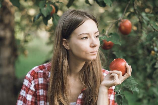 熟した有機リンゴを拾う美しい少女 Premium写真