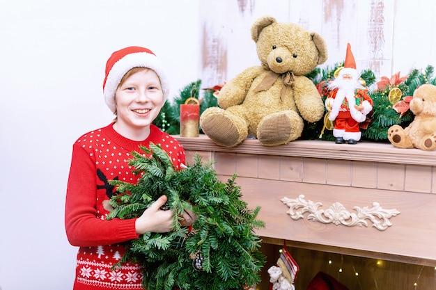 サンタの帽子の少年は、クリスマスや新年のリビングルームと暖炉を飾る。 Premium写真