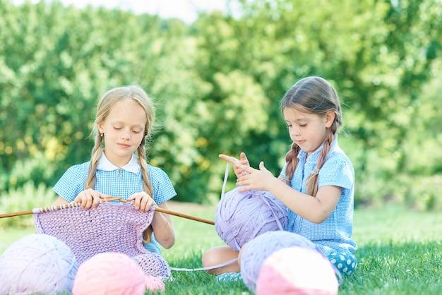 緑の芝生の上に座って、夏の日に針でセーターを編む子。 Premium写真