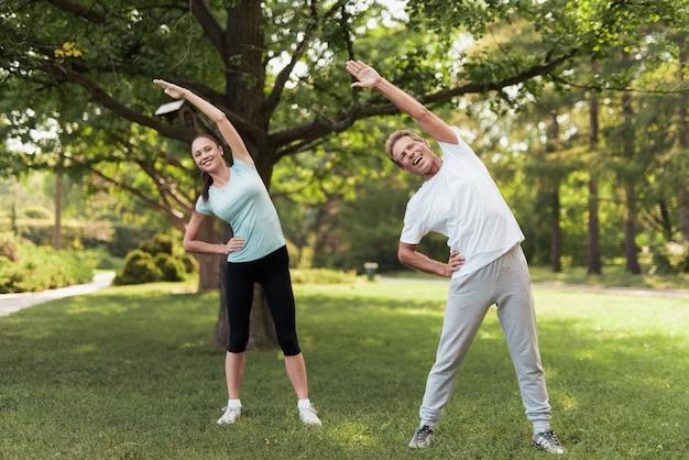 男と女が公園で練習をしています。彼らはウォームアップします。 Premium写真