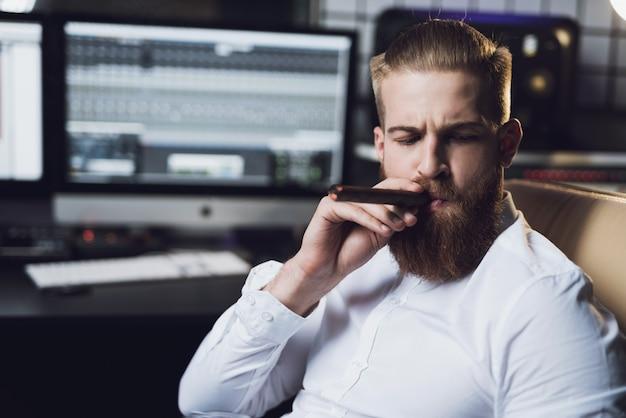 ひげを生やした男はスタジオに座って葉巻を吸っています。 Premium写真