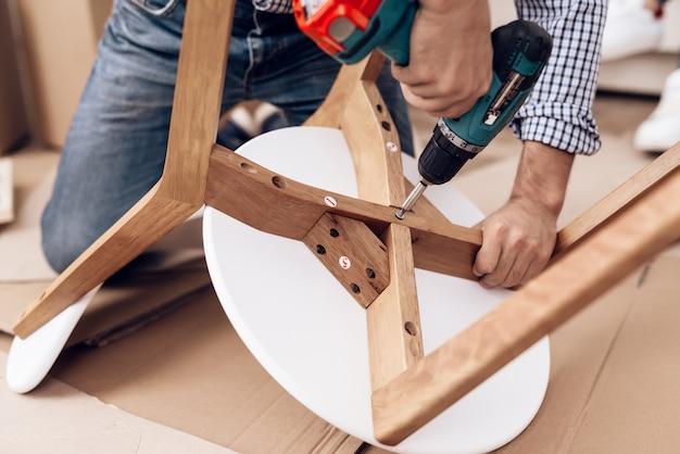 手にドリルを備えた家具組み立て業者が椅子を修理します。 Premium写真