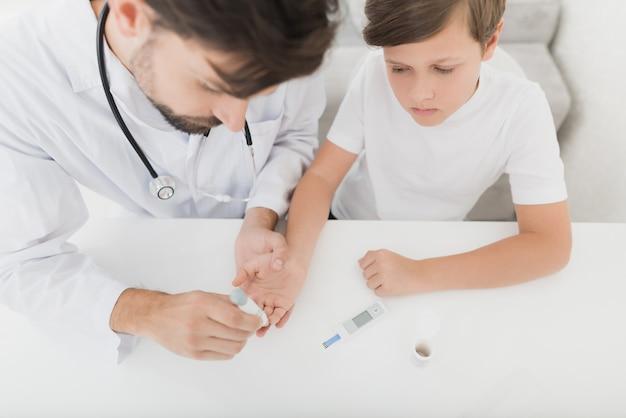 内分泌専門医が赤ちゃんの指から血液サンプルを採取します。 Premium写真