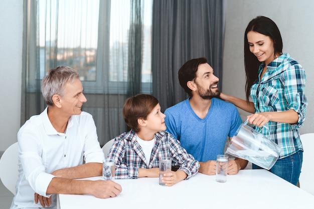 家族は家のホステスが新鮮な水を注ぐように見ています。 Premium写真