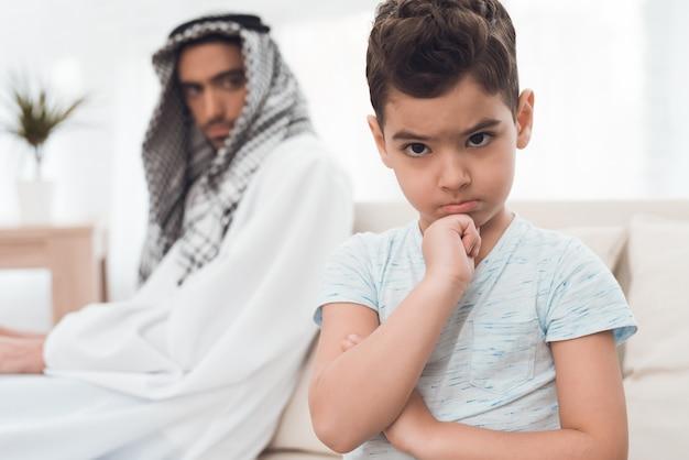 伝統的なアラブ家族の男の子は両親に腹を立てています。 Premium写真