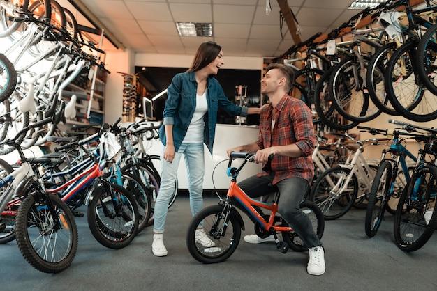 若い男と少女が子供用自転車を選択しています。 Premium写真