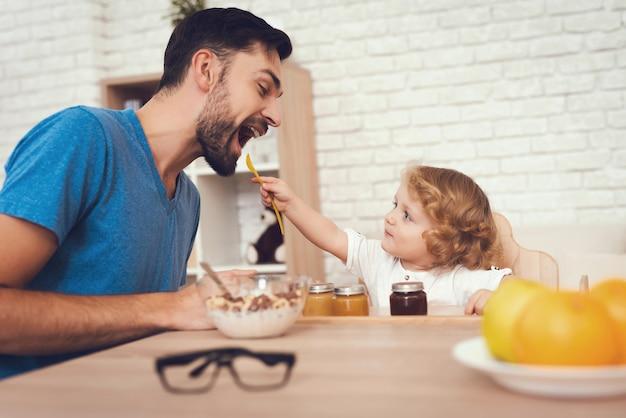 息子は父親に家で朝食を与えている。 Premium写真