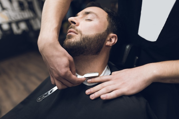 スタイリストは、古典的な鋭いカミソリを使用して、クライアントをきれいに剃ります。 Premium写真