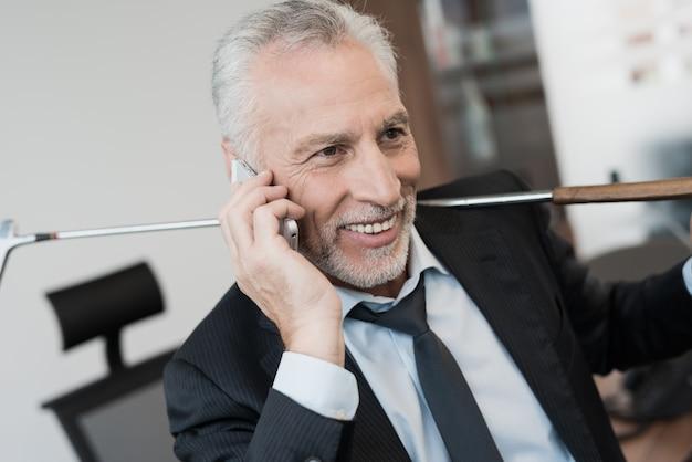 オフィスで電話で話している男性。 Premium写真