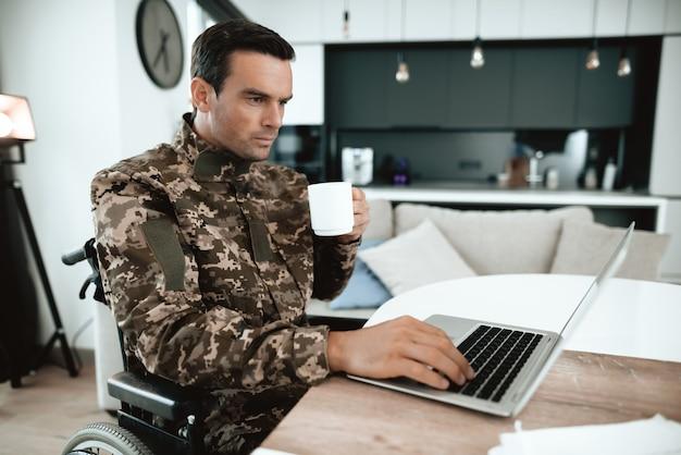車椅子の軍人は、屋内のラップトップで動作します。 Premium写真