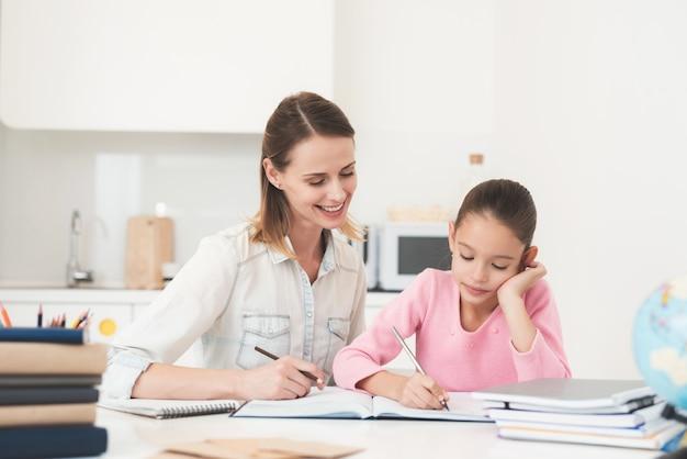 ママは娘が台所で宿題をするのを手伝ってくれます。 Premium写真