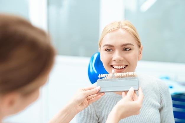 女性の歯科医は、患者の歯の色を決定します。 Premium写真