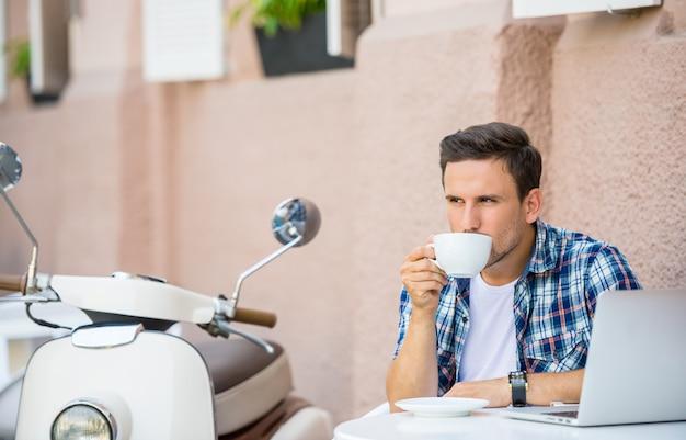 ハンサムな男はカフェでリラックスしてコーヒーを飲みます。 Premium写真