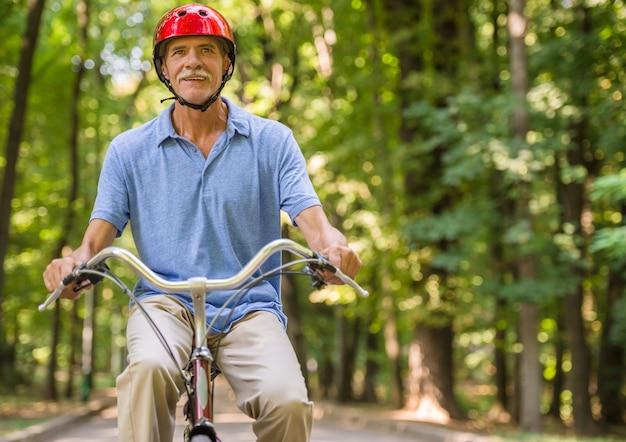 ヘルメットの年配の男性は公園で自転車に乗っています。 Premium写真
