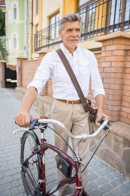 町の公道で彼の自転車を持つ年配の男性。 Premium写真