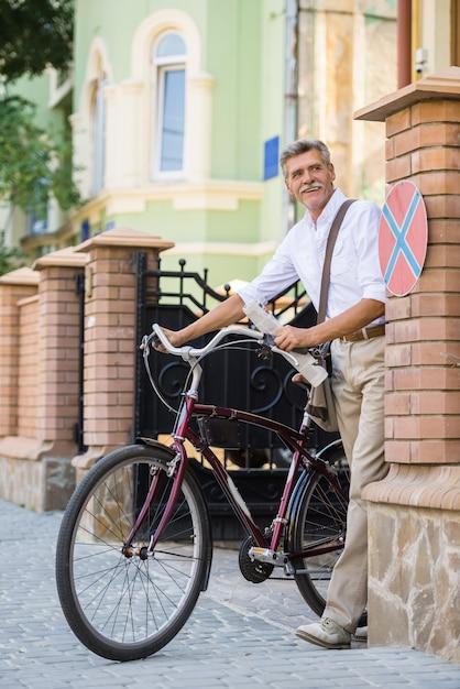 年配の男性は通りで自転車で歩いています。 Premium写真