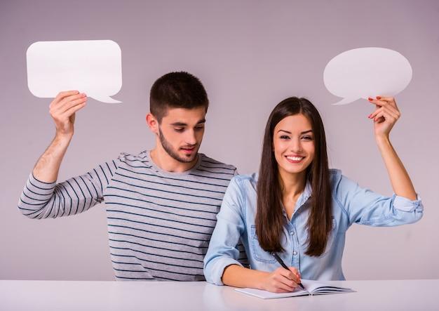 空のテキストバブルを保持しているテーブルに座って美しいカップル。 Premium写真