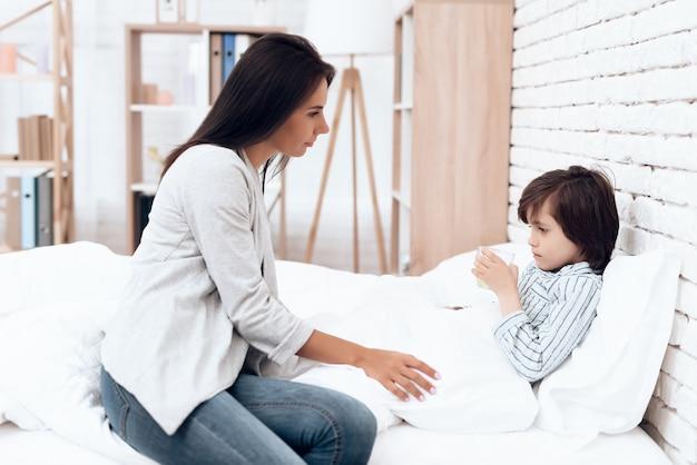 病気の息子横になっているベッドに薬を与える母 Premium写真