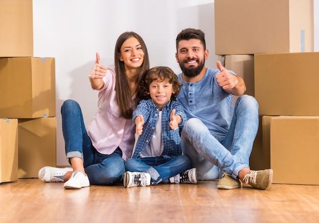若い幸せな家族が新しい家に移動し、ボックスを開きます。 Premium写真