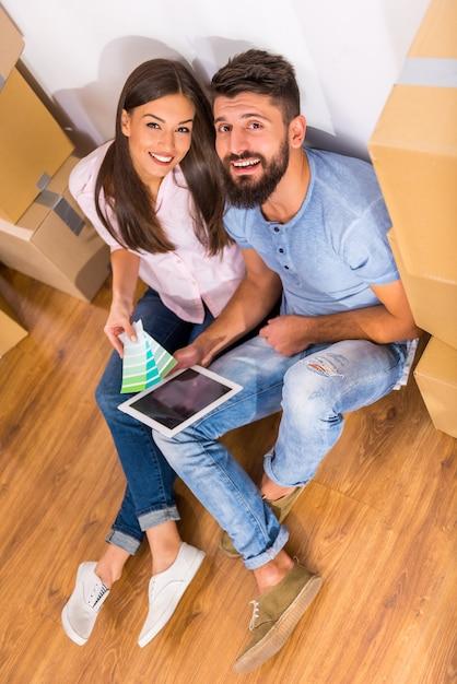新しい家で修理の準備をして若い幸せなカップル。 Premium写真