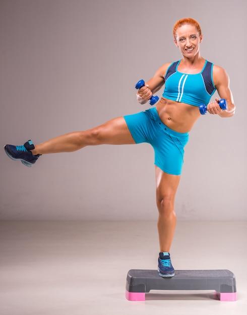 女性はステップボードにダンベルで運動をしています。 Premium写真