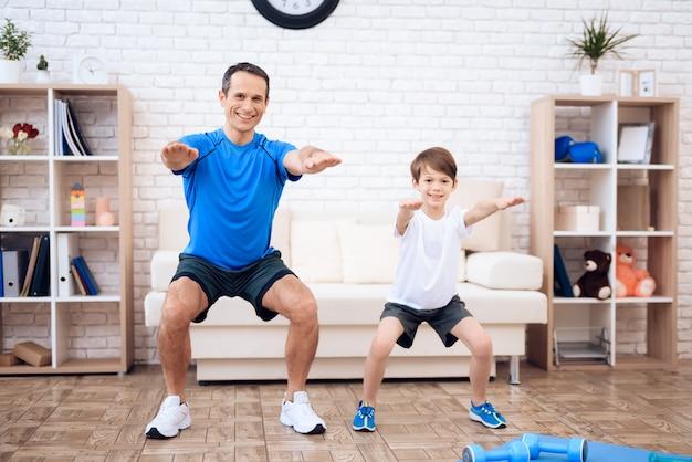 Счастливый отец и сын делают разминку делать приседания в домашних условиях. Premium Фотографии