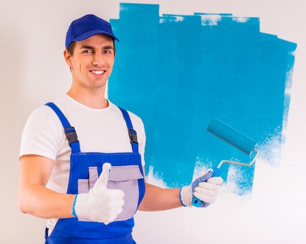 Мужской художник красит стену и показывает большой палец вверх. Premium Фотографии
