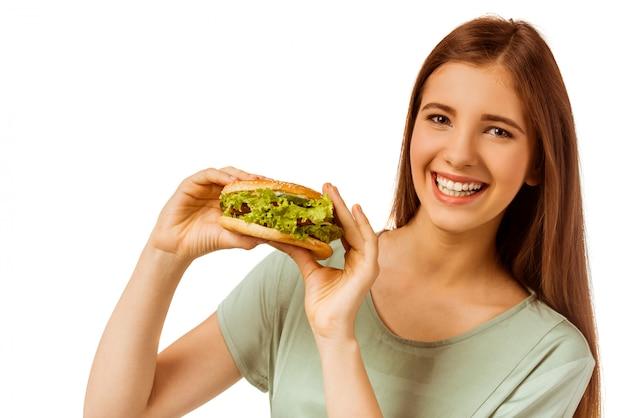 サンドイッチを食べる若い女の子のための健康食品。 Premium写真