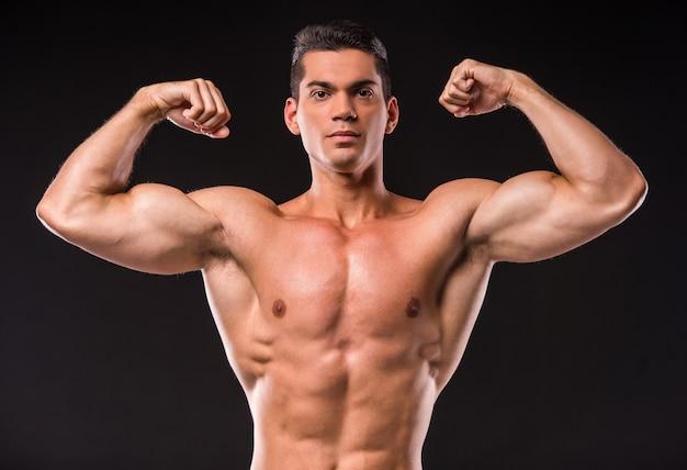 筋肉青年の肖像画は彼の筋肉を曲げています。 Premium写真