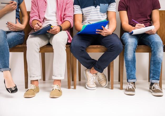 Группа людей, сидящих на стульях в ожидании интервью Premium Фотографии