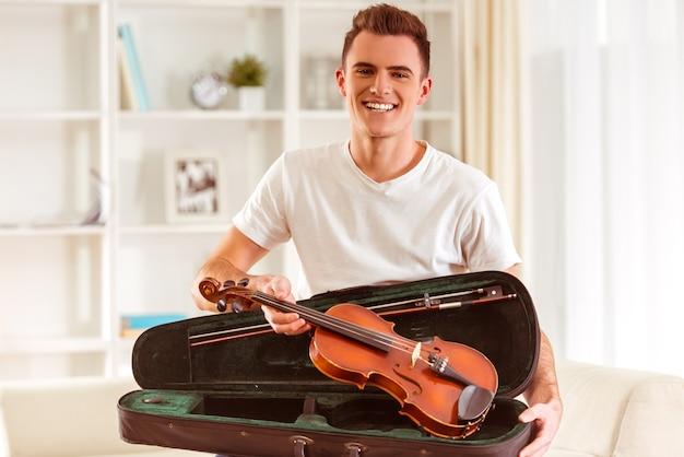 ソファに座ってバイオリンを持つ若い男性ミュージシャン。 Premium写真