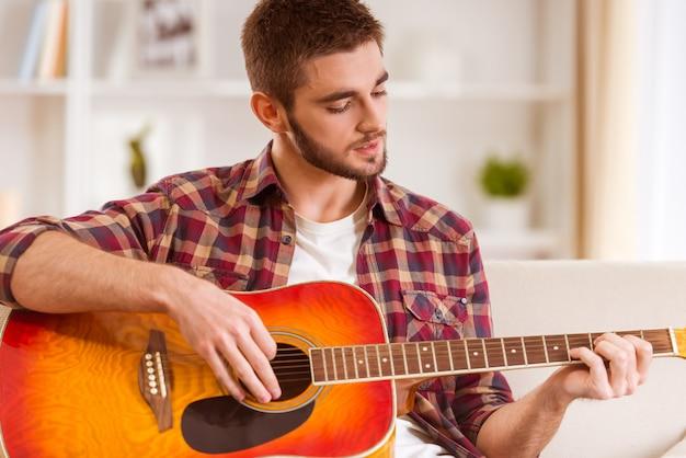 自宅でギターを弾く若い男の肖像画。 Premium写真