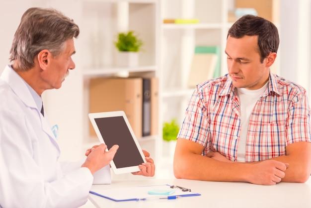 医者は患者に何かをタブレットで見せます。 Premium写真