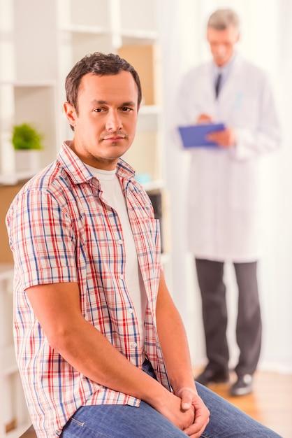 男が診療所に座って正面を見る。 Premium写真