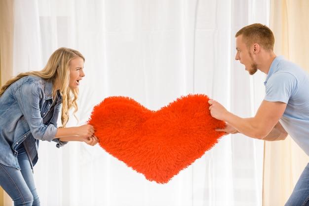 若いカップルはお互いに心を引っ張っています。 Premium写真