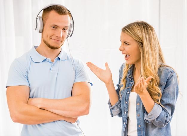 少女はヘッドフォンに立っている男に大声で叫ぶ。 Premium写真