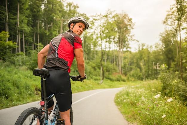 山の自転車に乗ってヘルメットの若い男。 Premium写真